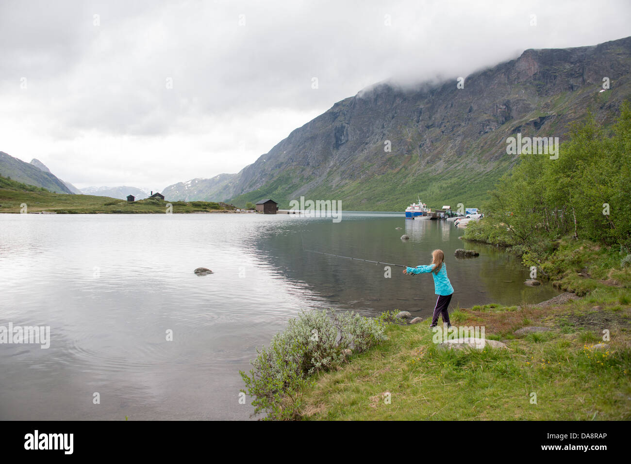 Fishing at the shores of the Gjende lake in Jotunheimen with the famous Besseggen hiking route in the background - Stock Image