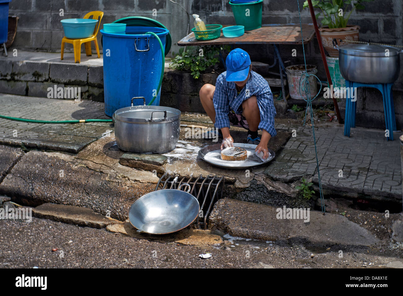 Person washing pots and pans on a Thai sidewalk. Thailand street scene. S. E. Asia - Stock Image