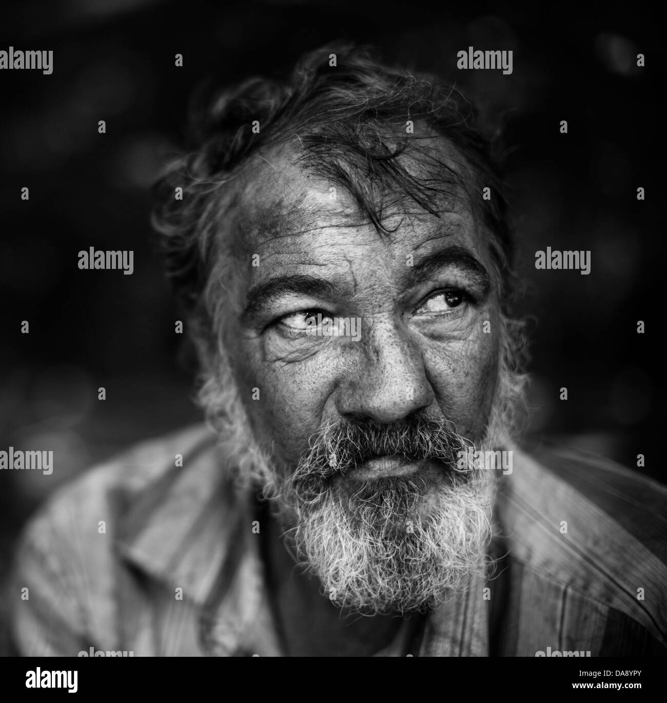 real homeless man on the dark background, selective focus on eye - Stock Image