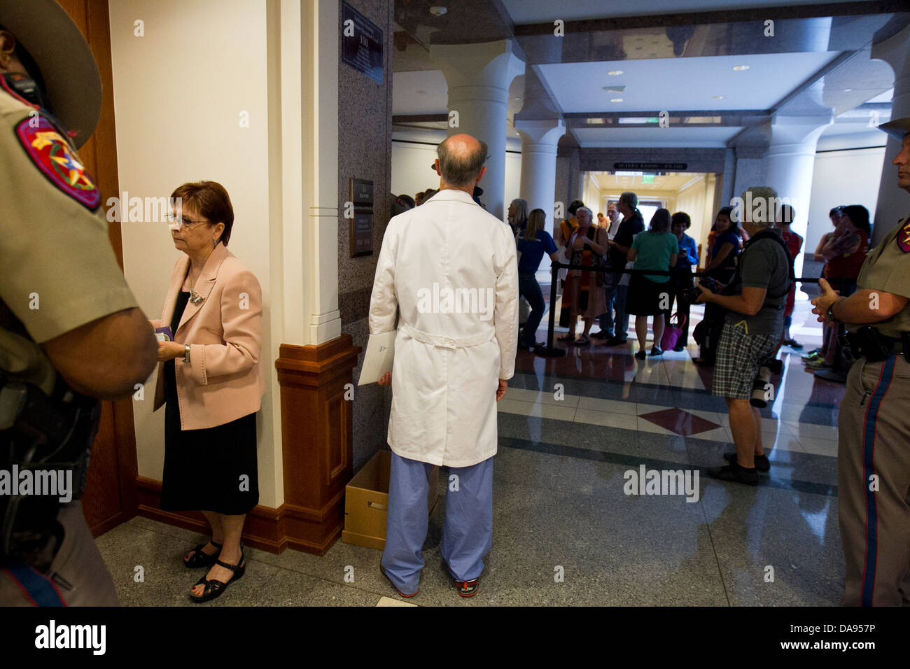 Medical doctor in white lab coat and scrubs stands in hallway of Texas Capitol building waiting for his turn to - Stock Image