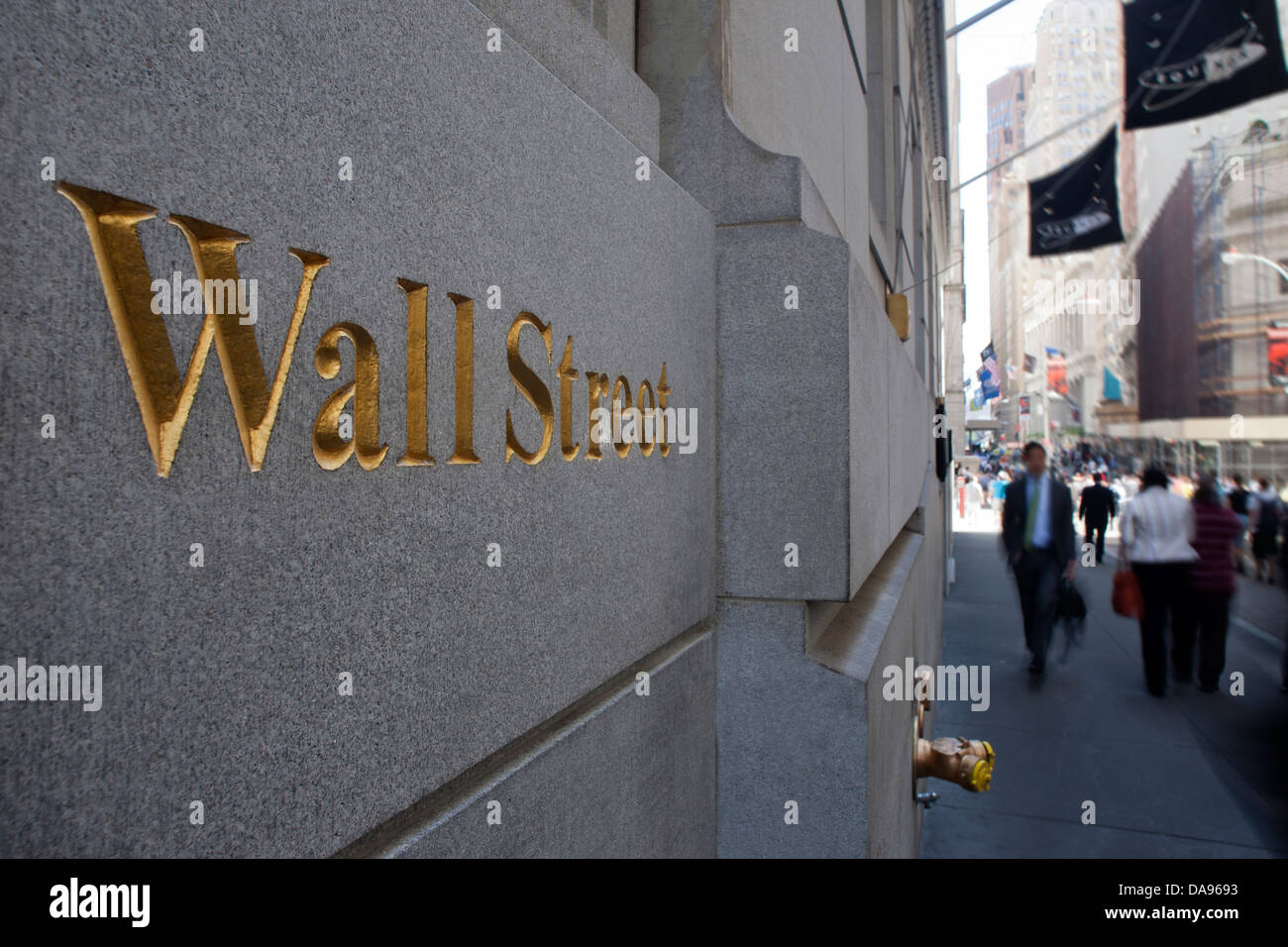 PEOPLE WALKING PAST WALL STREET SIGN DOWNTOWN MANHATTAN NEW YORK USA - Stock Image