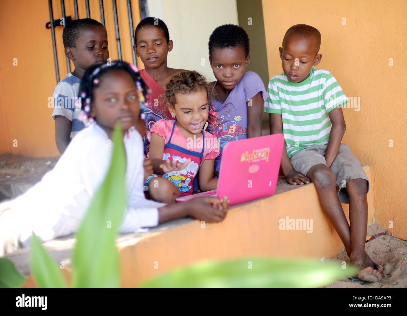 Children sit around an educational computer on Inhaca Island in Mozambique, 23 February 2013. Photo:Britta Pedersen Stock Photo