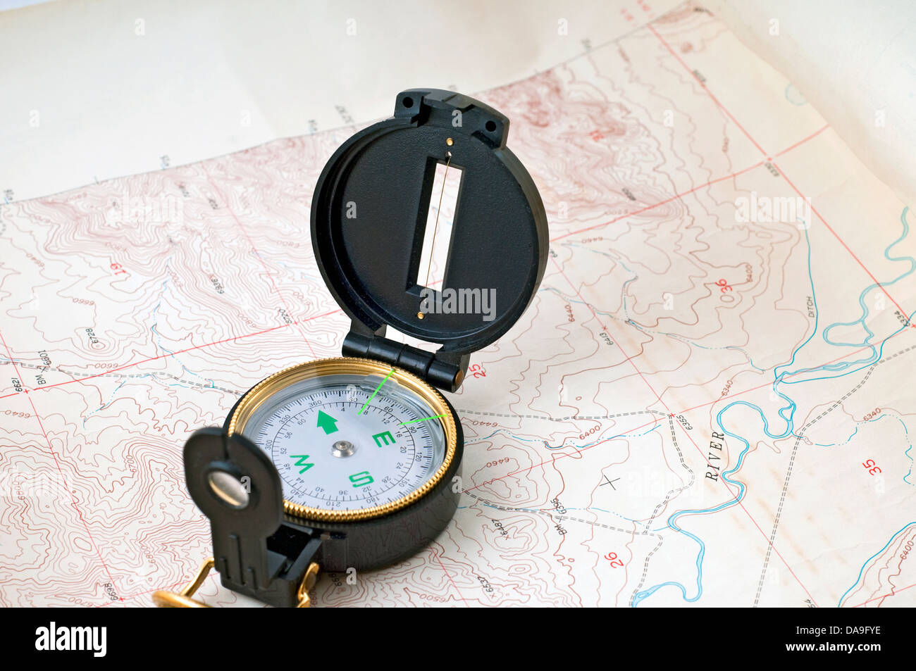 compass laid out over a topographical map - Stock Image