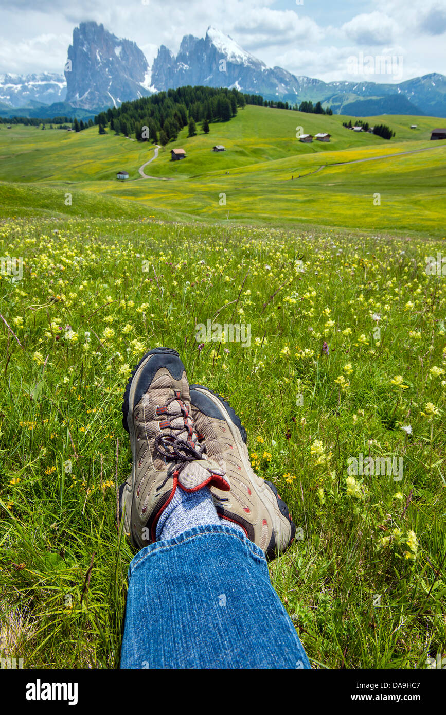 Crossed legs of a hiker at Alpe di Siusi or Seiser Alm with Sassolungo mountain behind, Dolomites, Alto Adige South - Stock Image