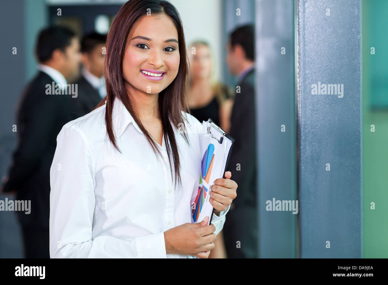 portrait of attractive secretary standing in meeting room holding a clipboard - Stock Image