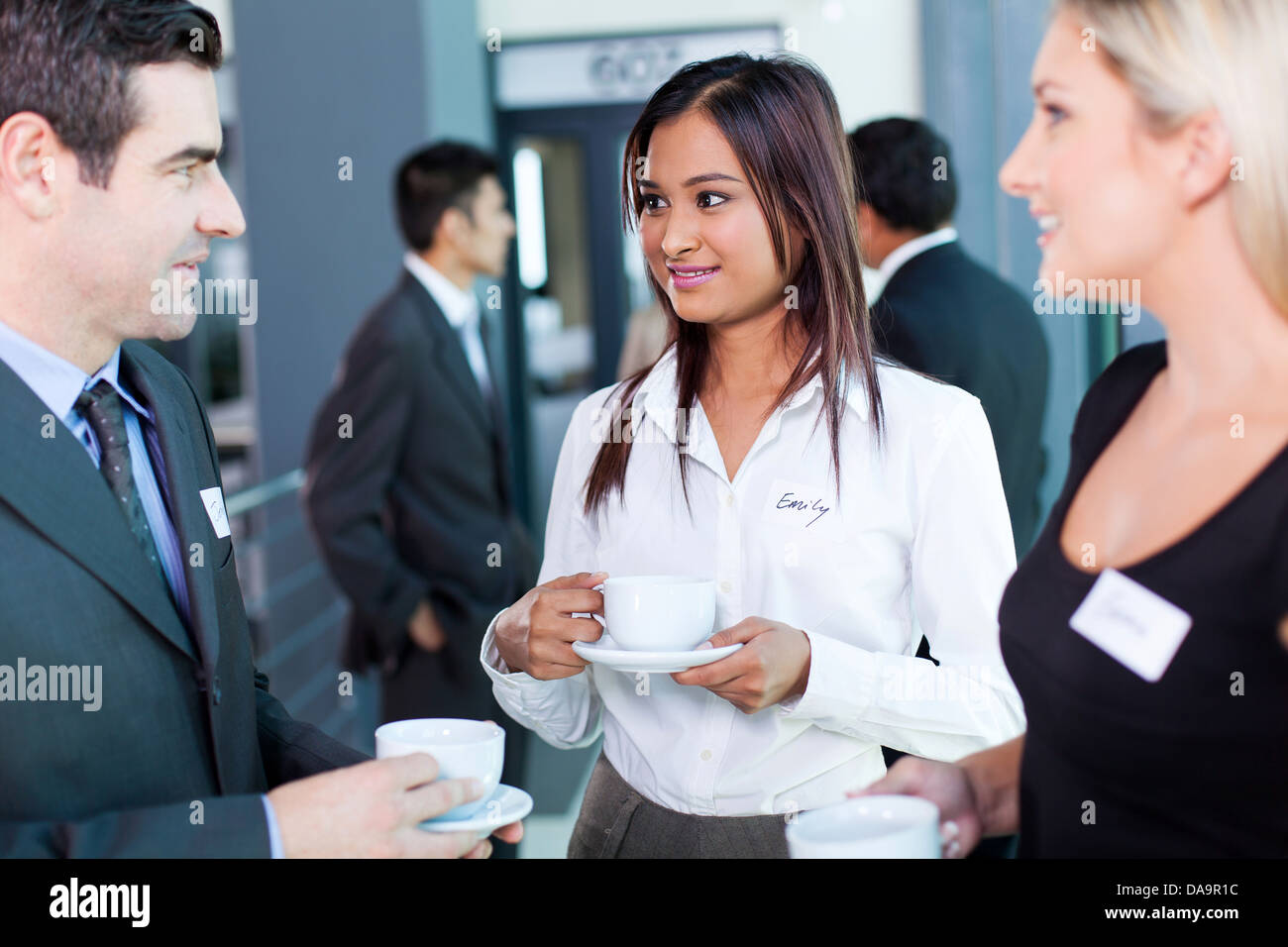 businesspeople interacting during coffee break at business conference - Stock Image