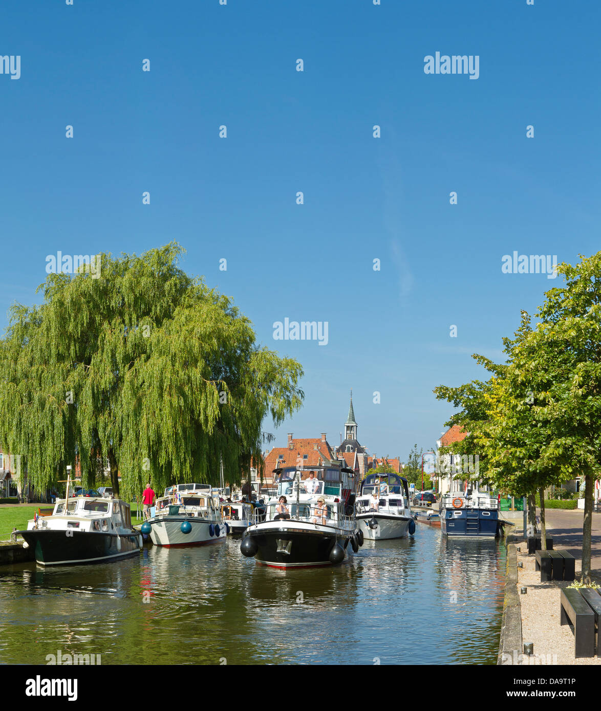 Netherlands, Holland, Europe, Makkum, Shipping, historic, centre, city, village, water, trees, summer, people, ships, - Stock Image