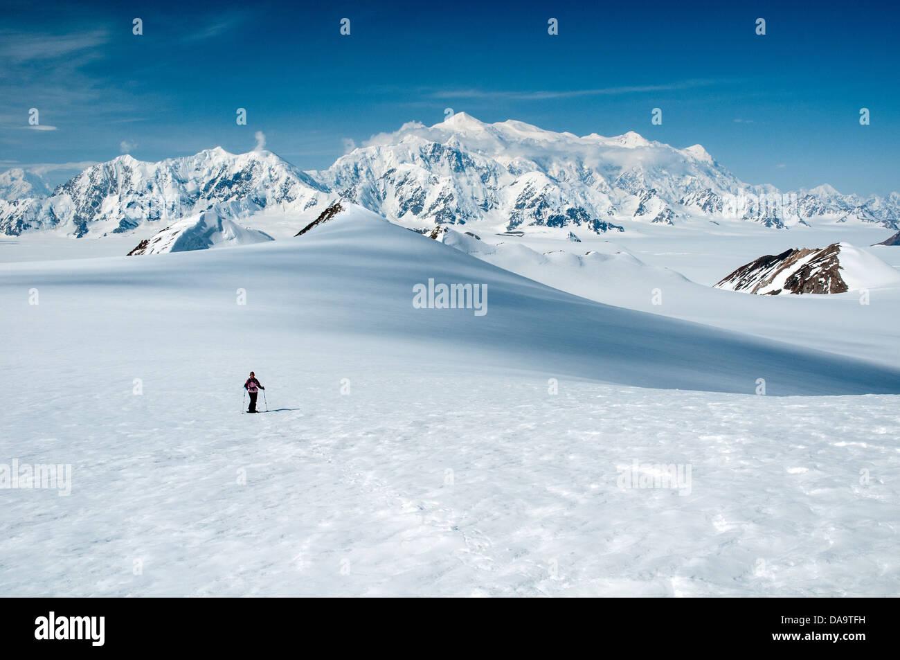 A snowshoer treks through Yukon's St. Elias Mountains, with Mount Logan, Canada's highest peak, in the background. - Stock Image