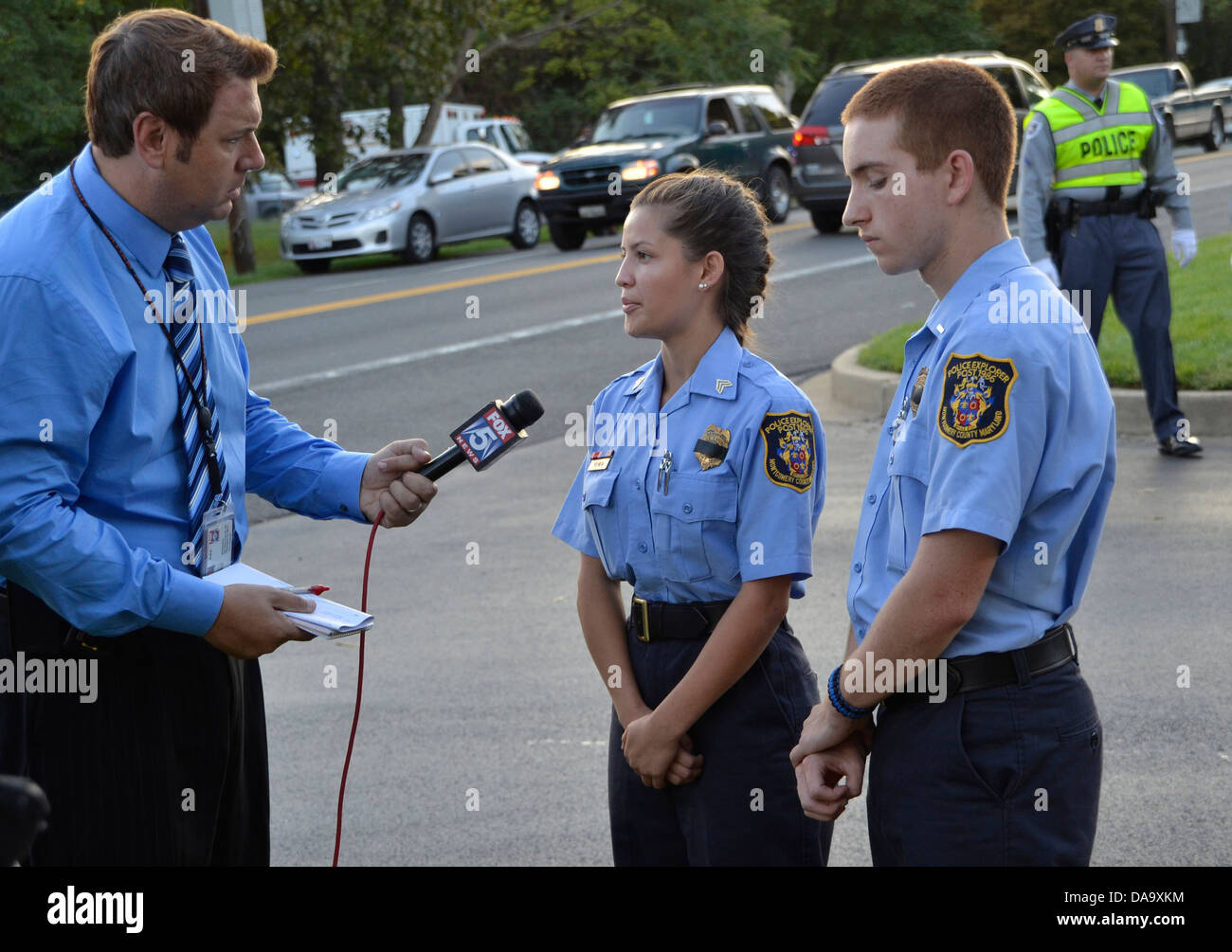 A TV reorter interviews two police cadets at the funeral for a policeman killed in the line of duty Beltsville, - Stock Image