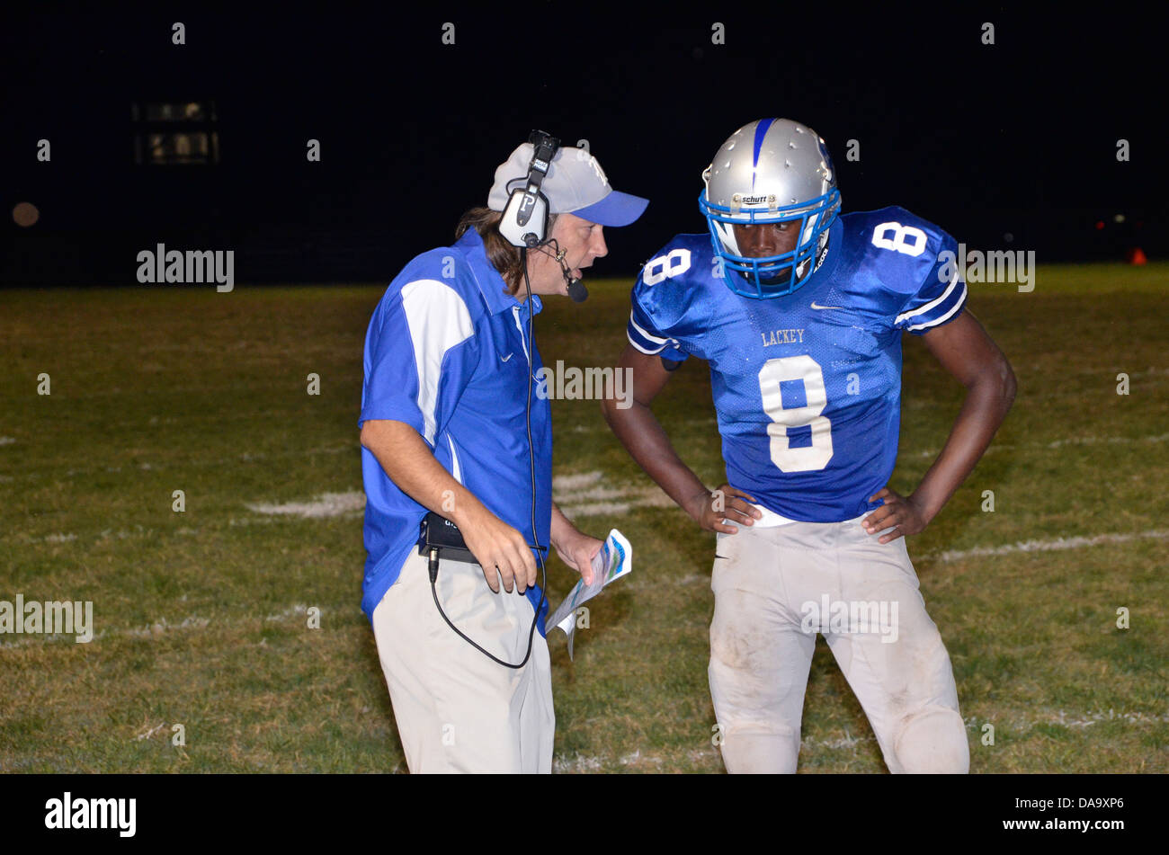 Coach discussing strategy with his quarterback in a nighttime high school football game - Stock Image