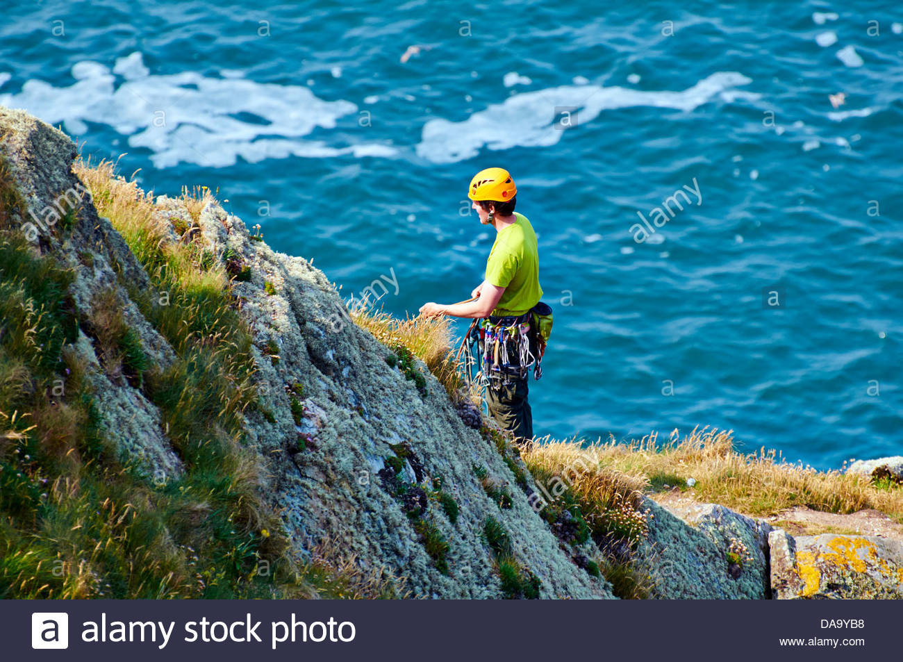 male rock climber yellow safety helmet holding rope while climbing rocks on wales rocky coastline in anglesey north - Stock Image