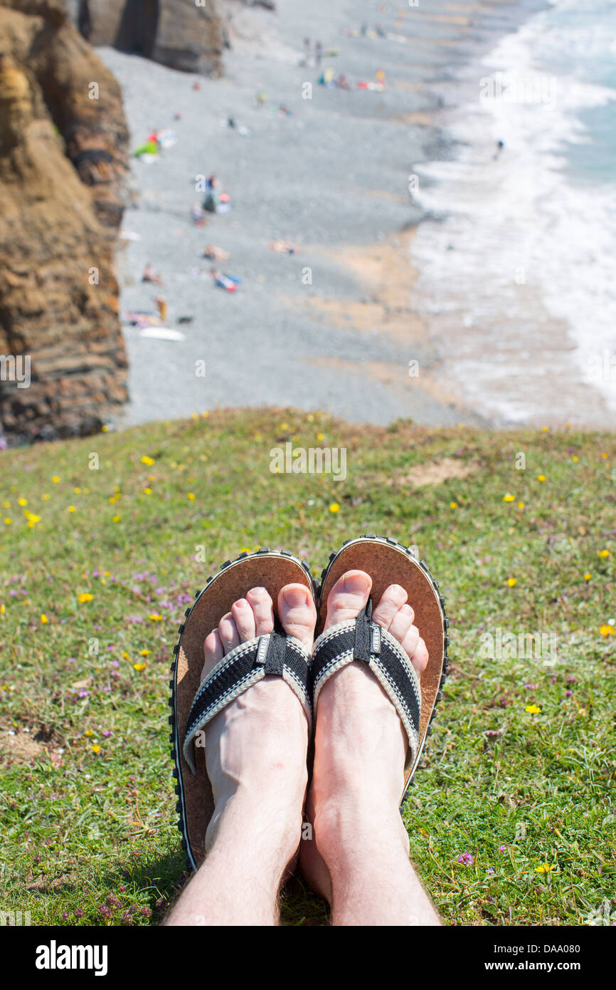 fd73dccb11bab3 Men s feet wearing a pair of flip flop sandals on a cliff top above  Sandymouth Bay