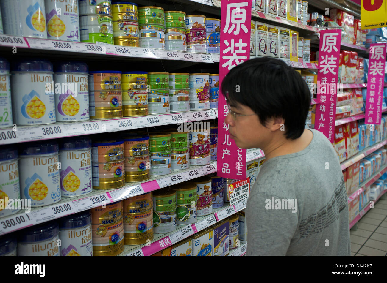 A man looks at imported infant formula baby milk powder in a supermarket in Beijing, China. 09-Jul-2013 Stock Photo