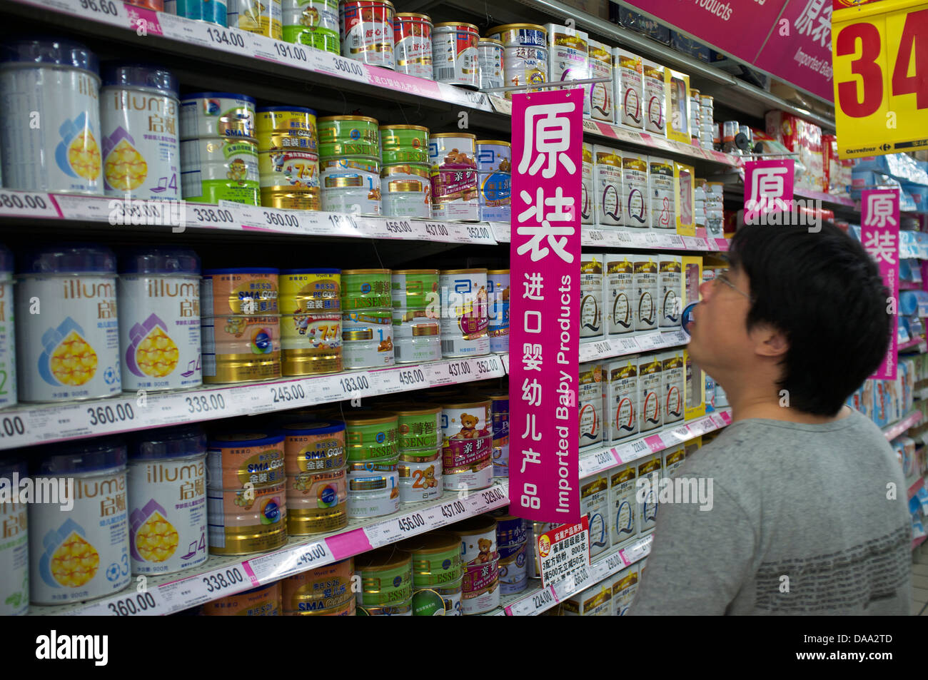 A man looks at imported infant formula baby milk powder in a supermarket in Beijing, China. 09-Jul-2013 - Stock Image