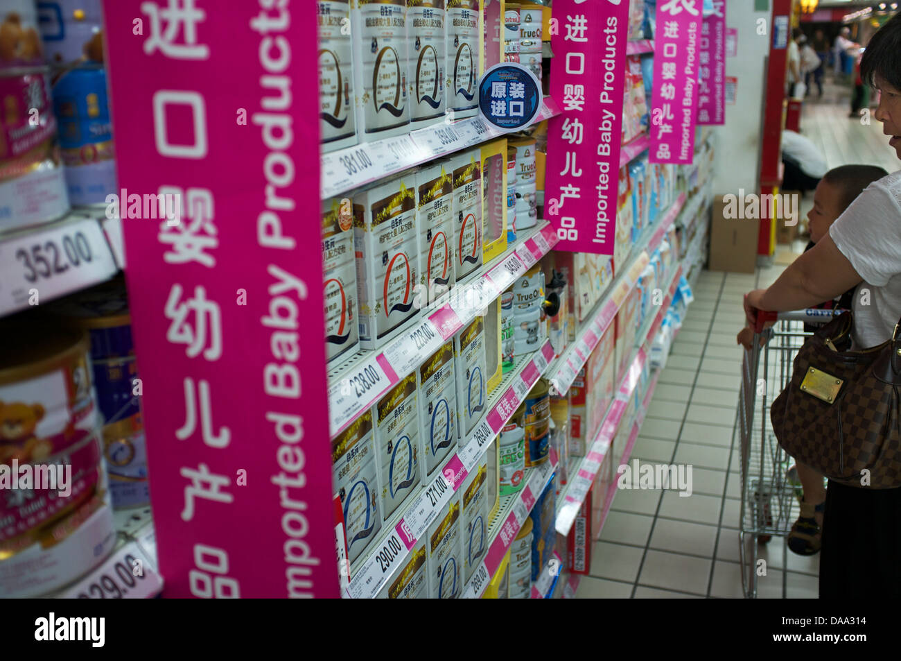 An elderly woman and a baby look at imported infant formula baby milk powder in a supermarket in Beijing, China. - Stock Image