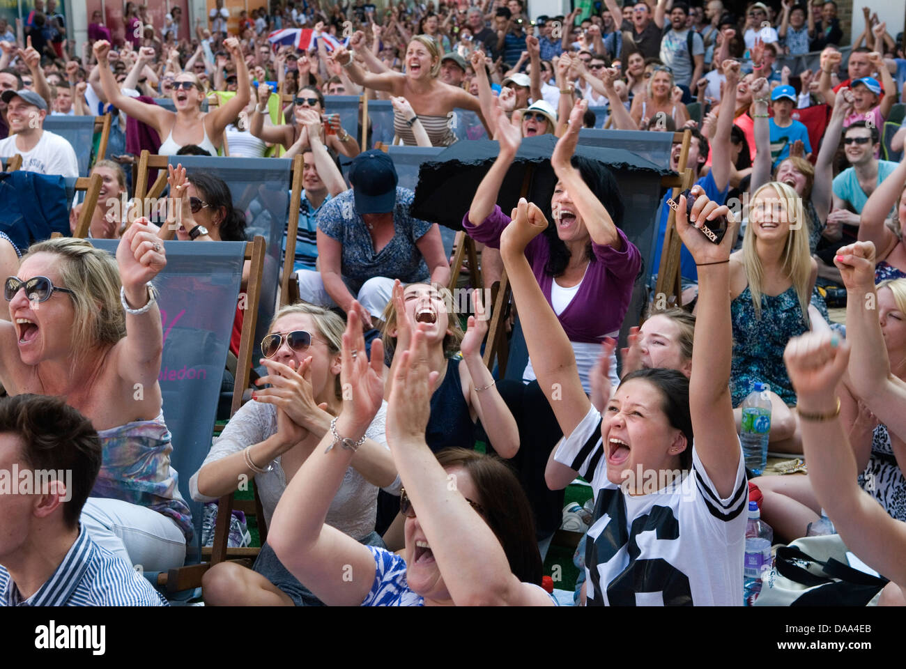 Watching sport  Cheering crowd of sports fans Wimbledon town center watching on TV screen UK HOMER SYKES - Stock Image