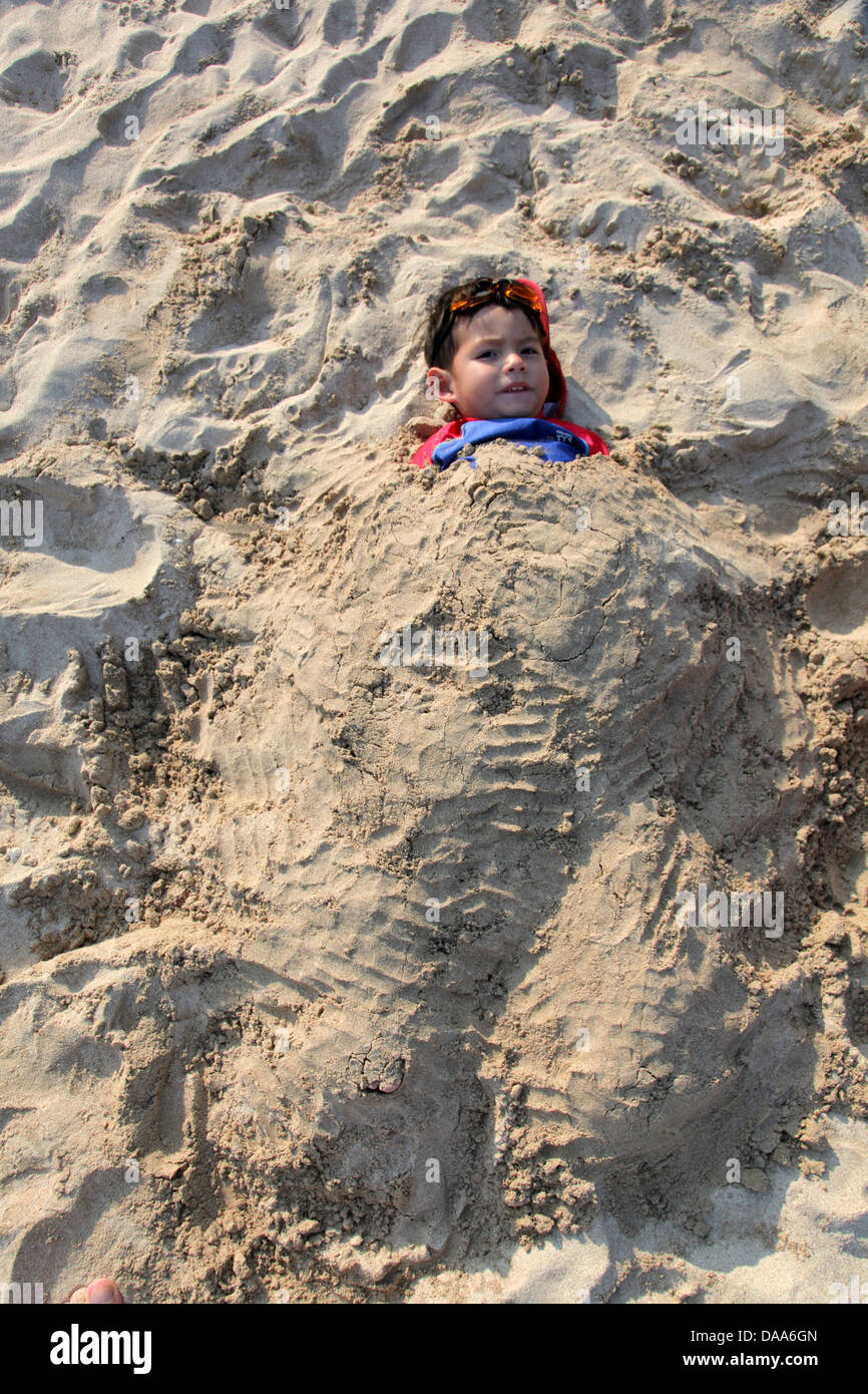 It's a photo of a kid cover in sand or silt or bury in the sand beach for fun Stock Photo