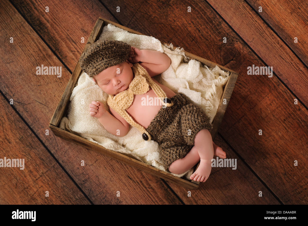 Newborn Baby Boy Wearing a Hat, Bow Tie and Suspenders - Stock Image