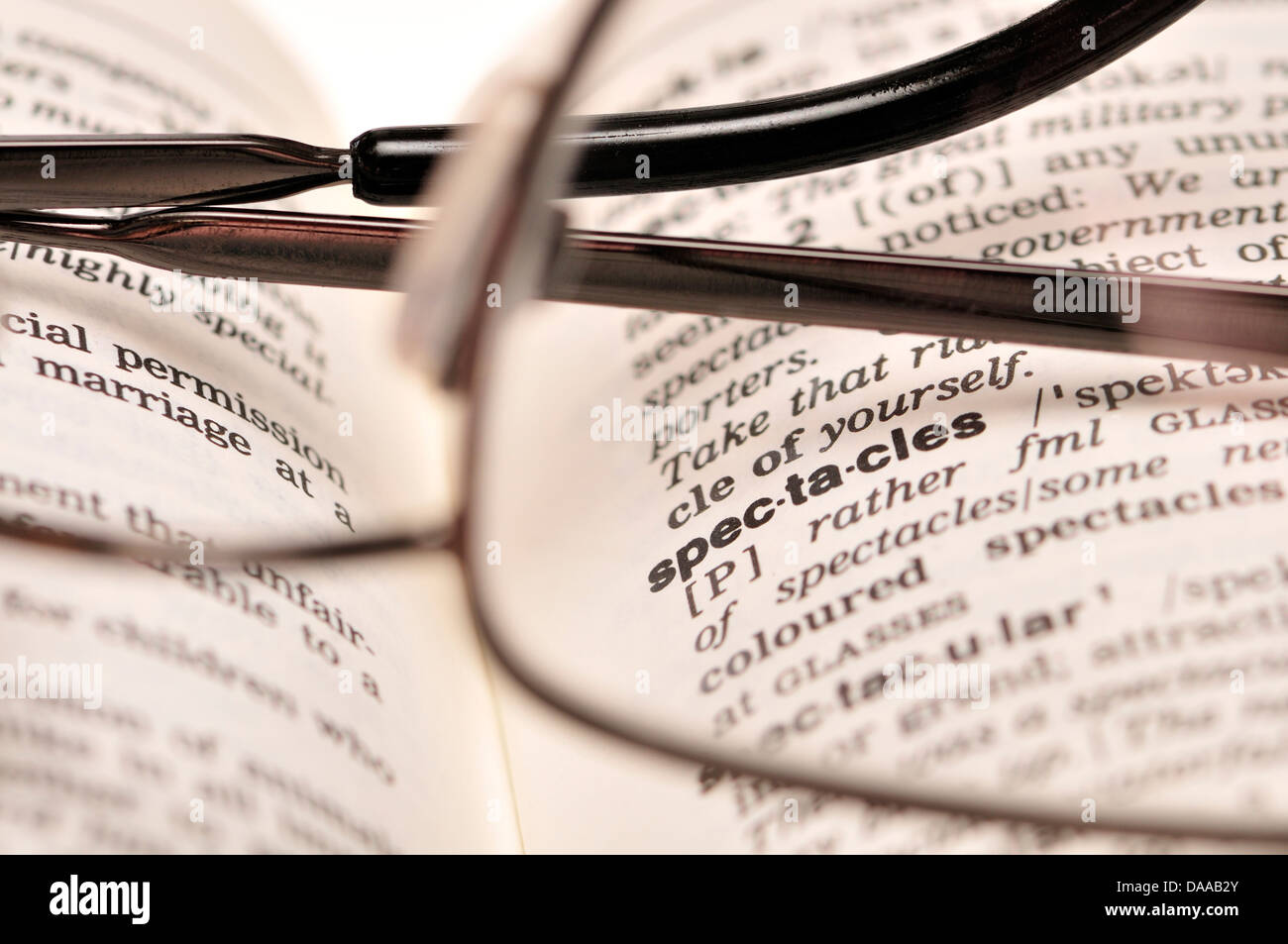 Pair of glasses on a dictionary open at 'spectacles' - Stock Image
