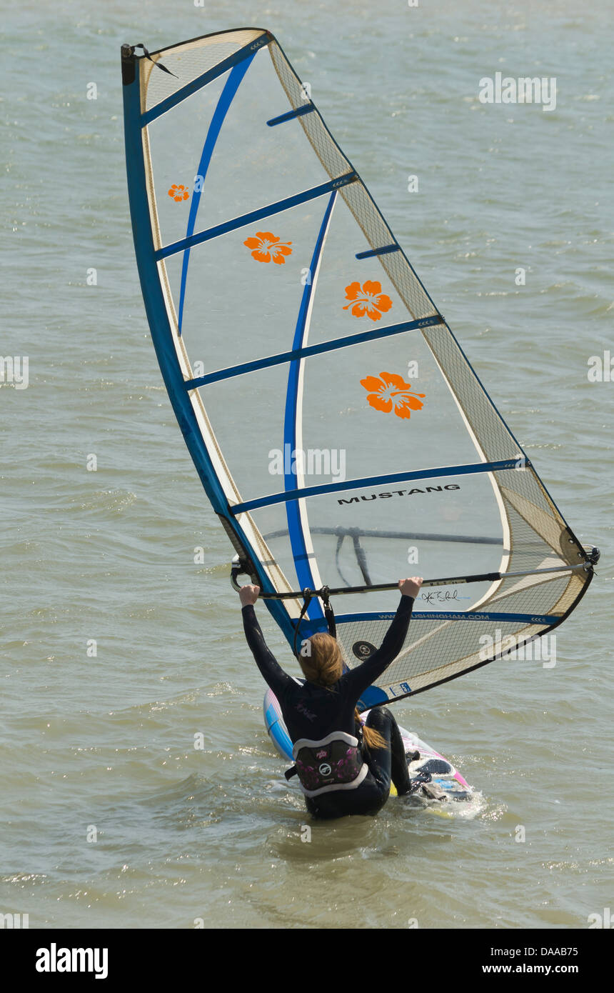 woman getting onto her sailboard Stock Photo