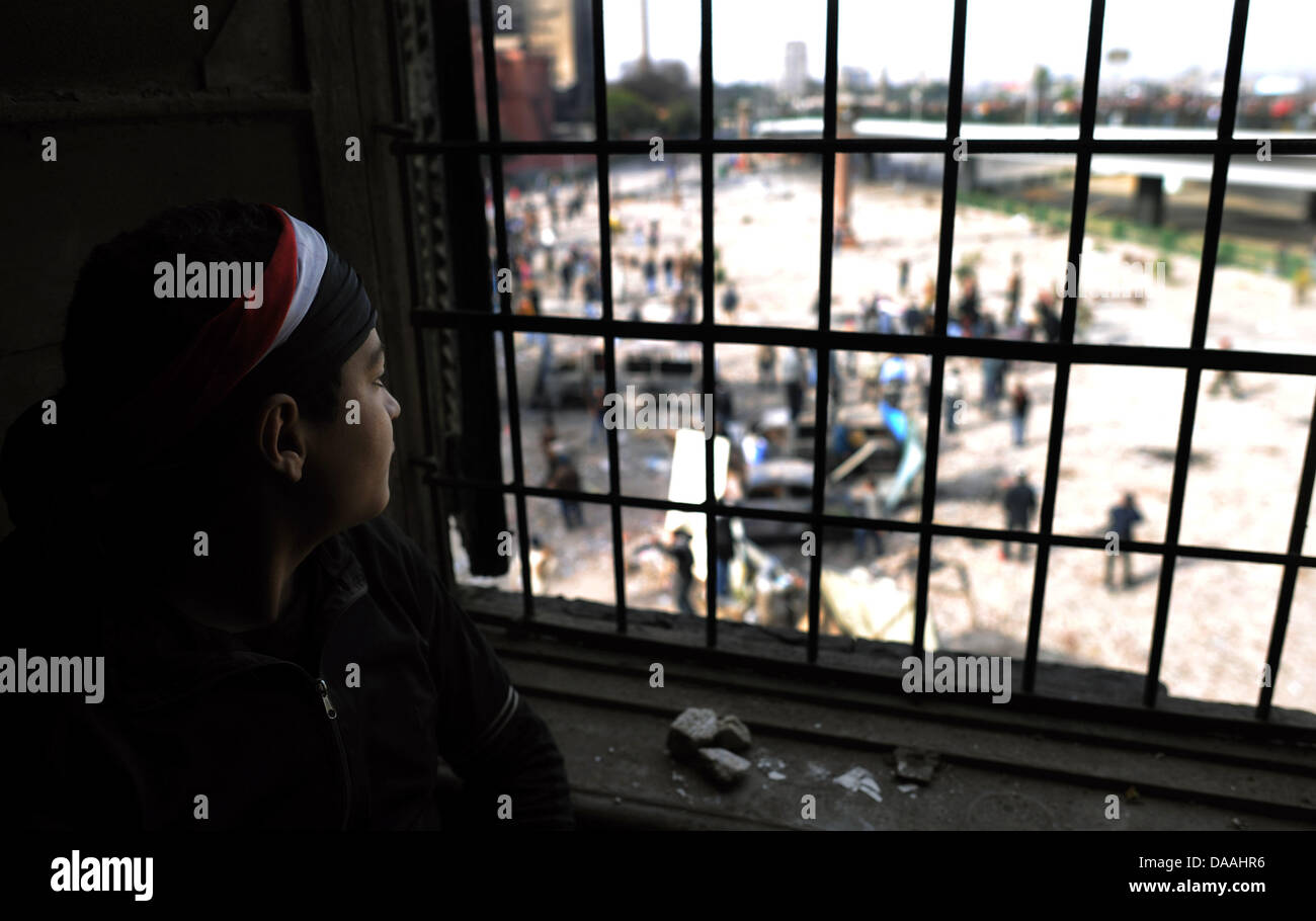 A young boy observes proponents of Hosni Mubarak demononstrate next to the national museum with a barricade at an Stock Photo