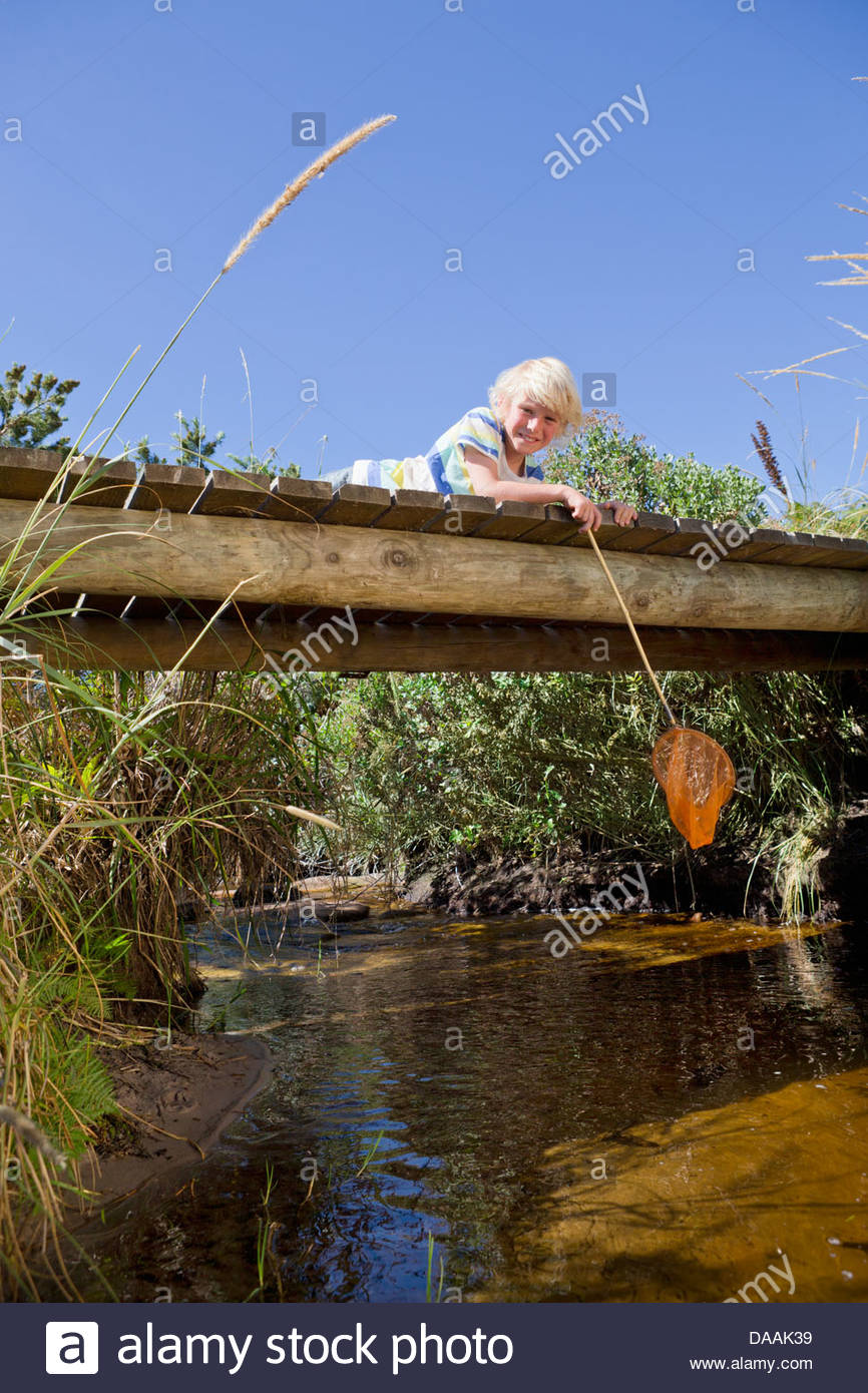 Portrait of smiling boy with fishing net laying on footbridge over stream - Stock Image