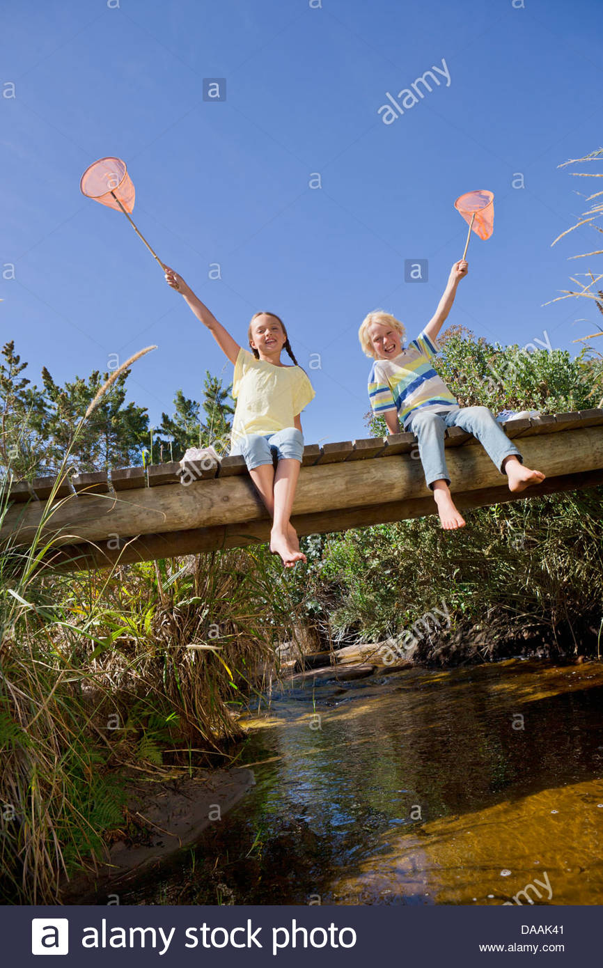 Portrait of smiling boy and girl hold fishing nets overhead on footbridge over stream - Stock Image