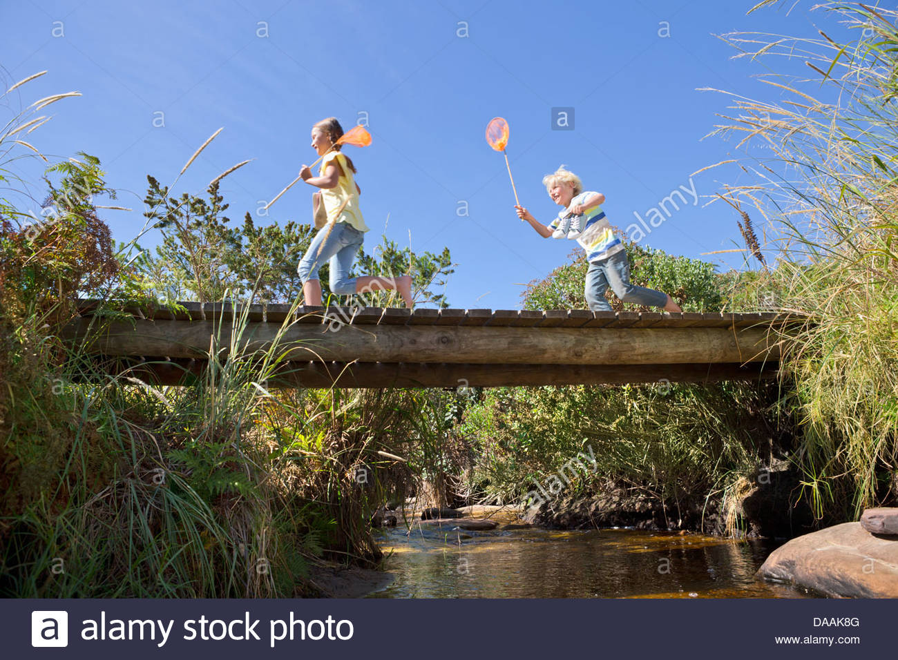 Happy boy and girl with fishing nets running on footbridge over stream - Stock Image