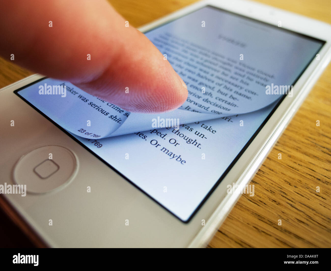 Detail of iPhone 5 smart phone screen showing iBooks ebook reader with page turning Stock Photo