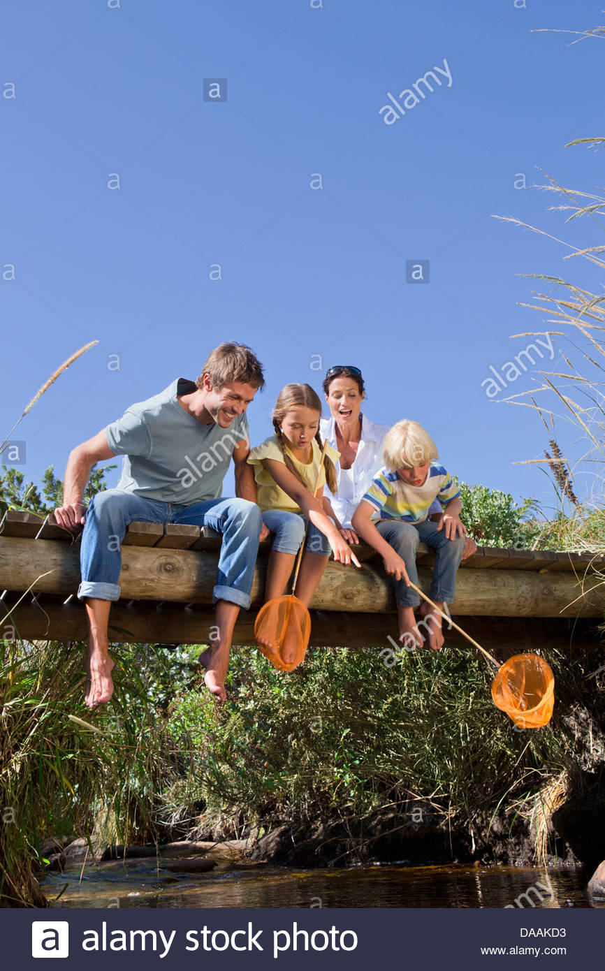 Family with fishing nets sitting on footbridge and looking down at stream - Stock Image