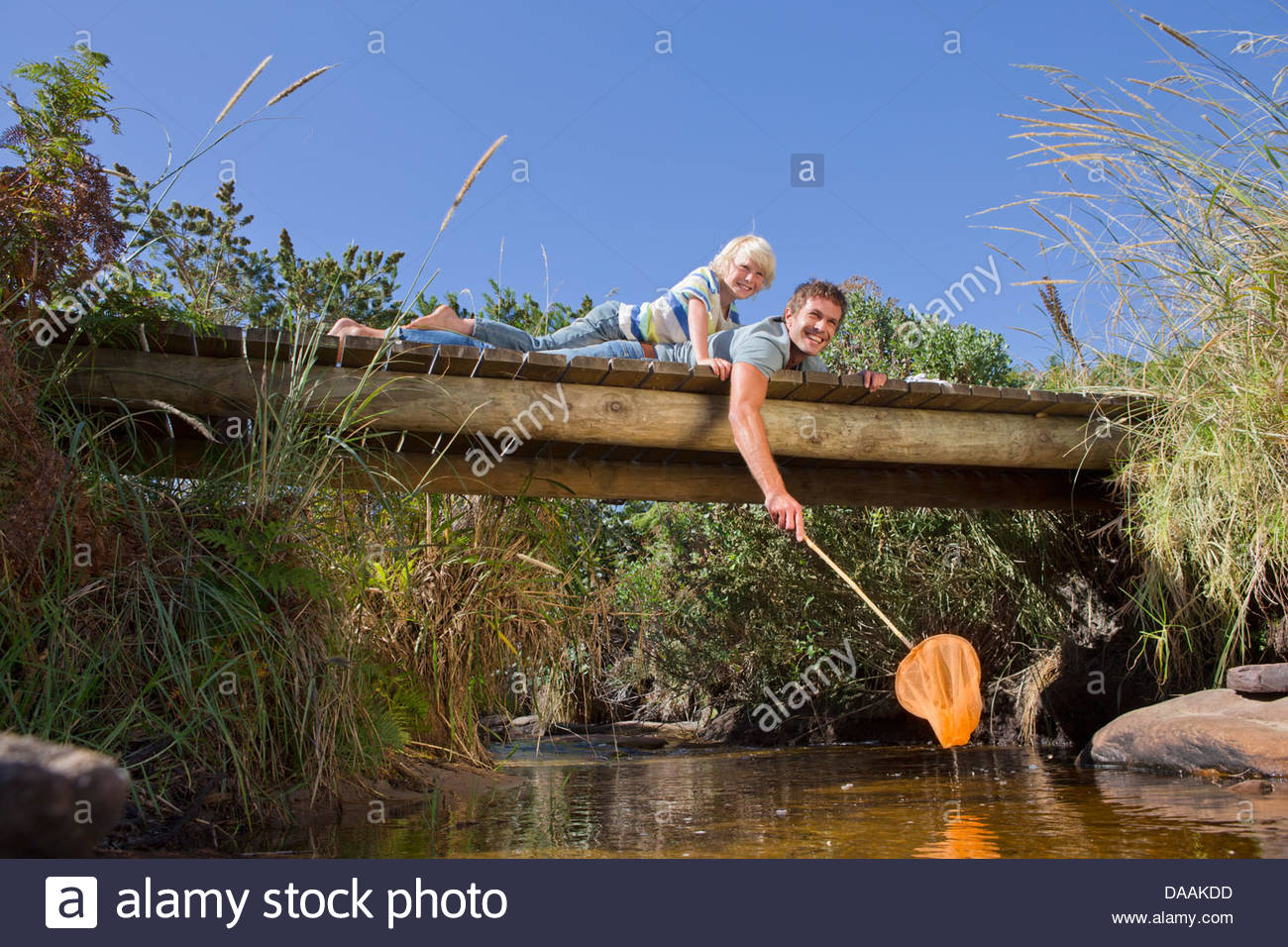 Portrait of smiling father and son with fishing net laying on footbridge over stream - Stock Image