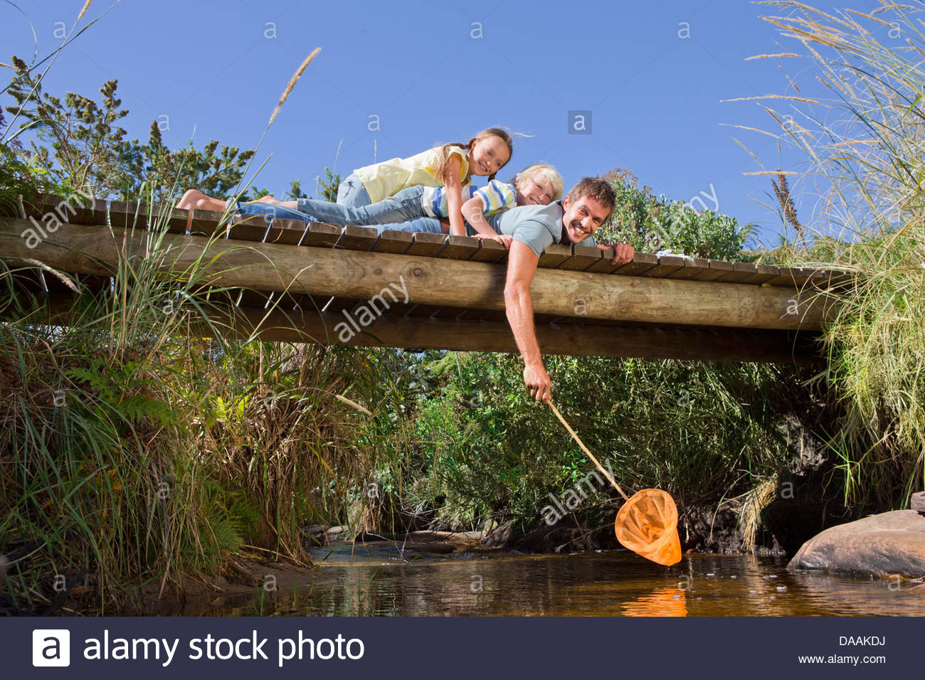Portrait of smiling father, daughter and son with fishing net laying on footbridge over stream - Stock Image