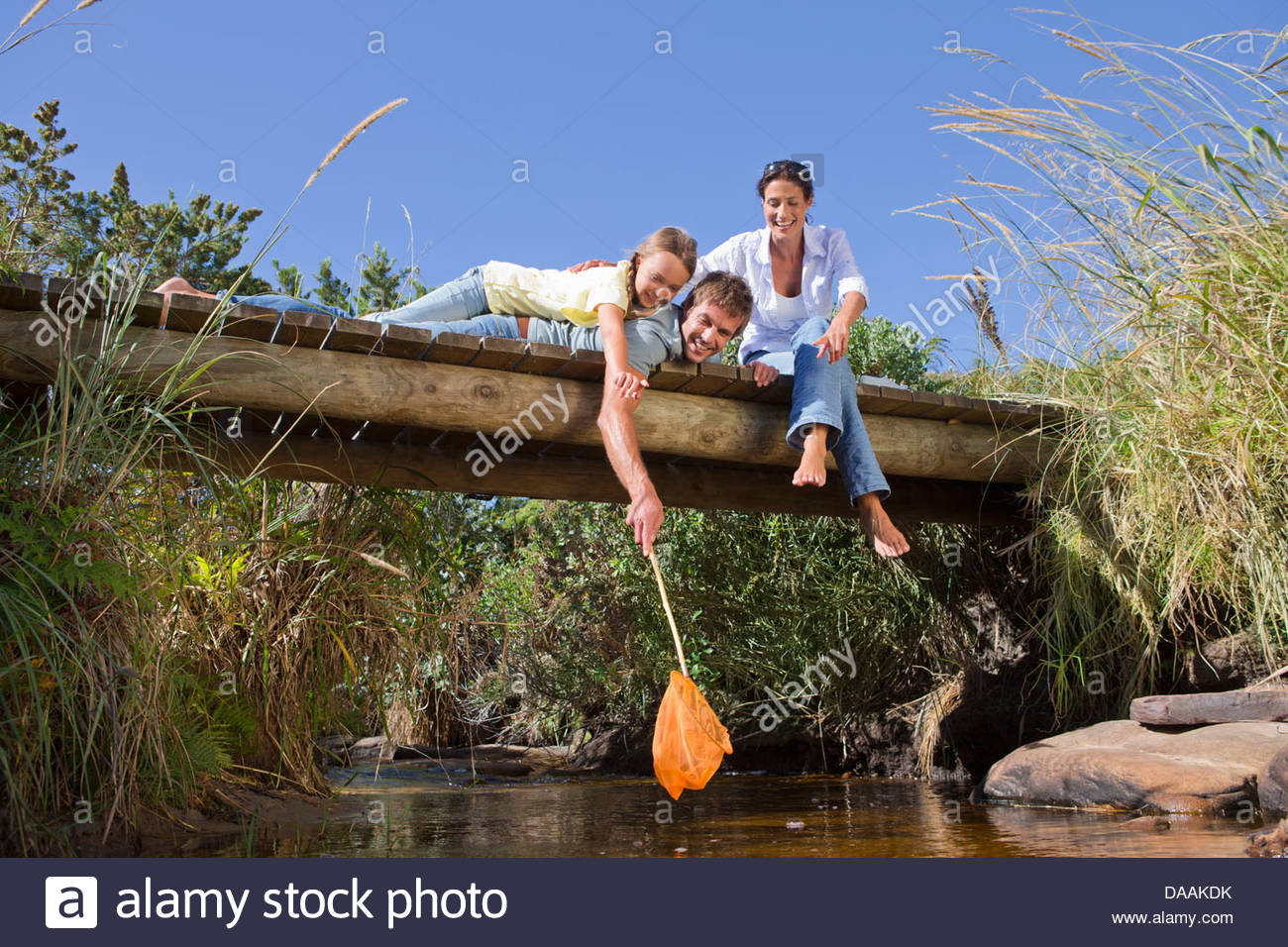 Smiling family with fishing net on footbridge over stream - Stock Image