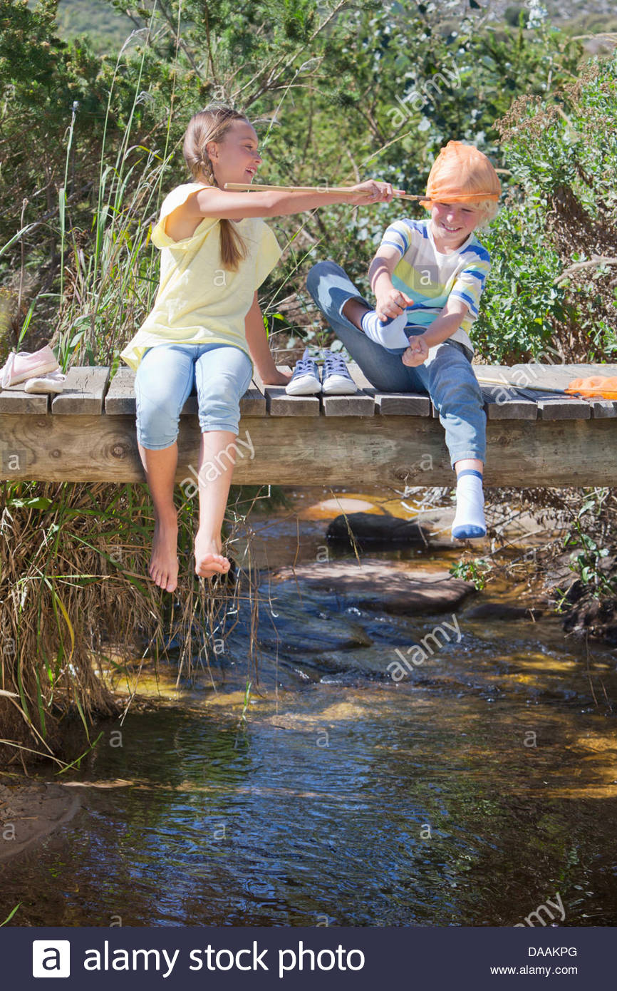Boy and girl playing with fishing net on footbridge over stream - Stock Image