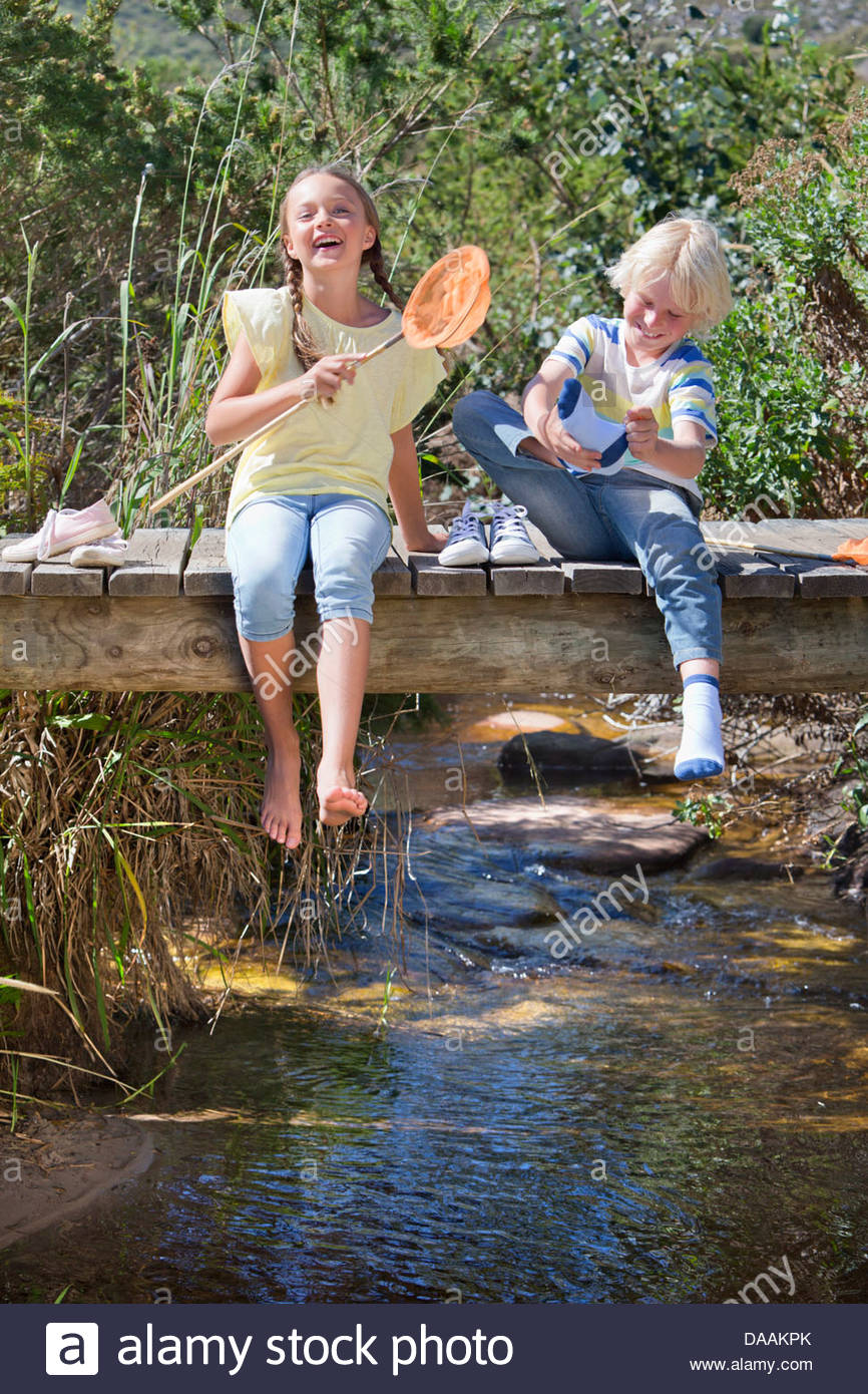Happy boy and girl with fishing net removing shoes and socks on footbridge over stream - Stock Image