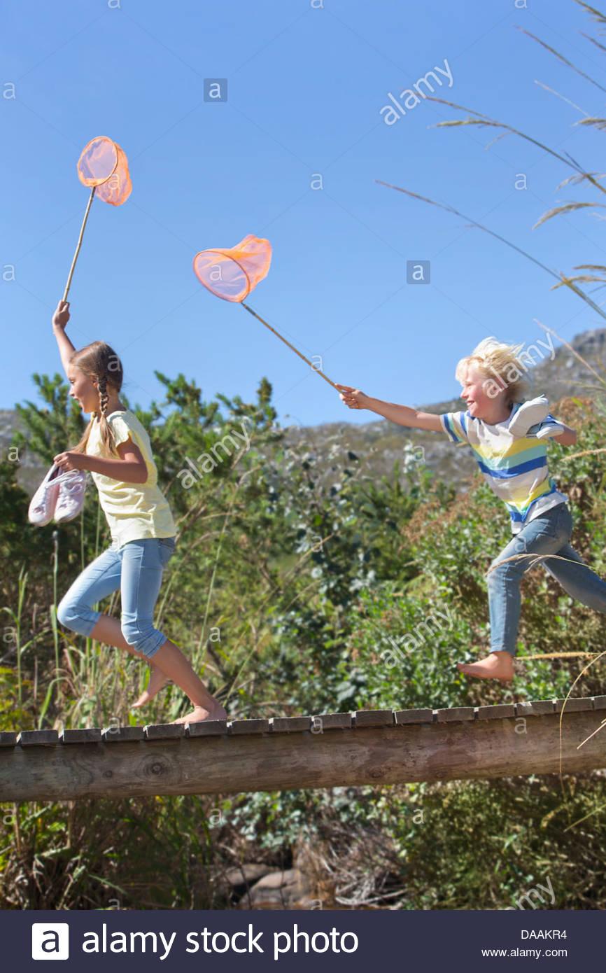 Boy and girl running barefoot with fishing nets on footbridge - Stock Image