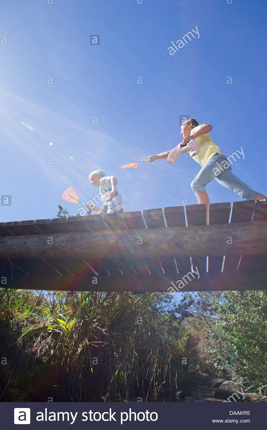 Girl chasing boy with fishing net on footbridge - Stock Image