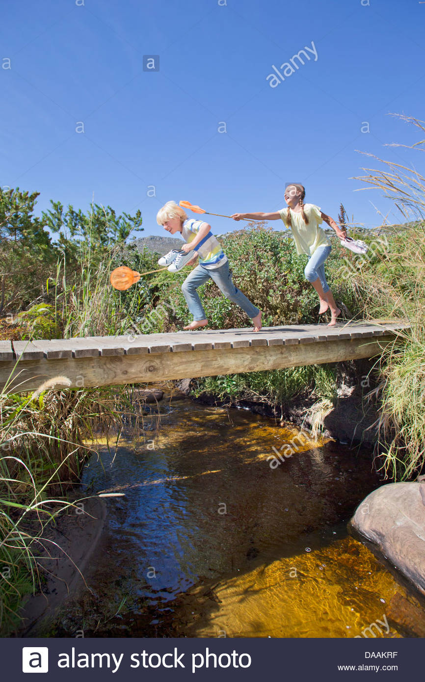 Girl chasing boy with fishing net on footbridge over stream - Stock Image
