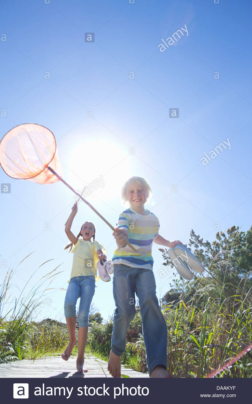 Enthusiastic boy and girl holding fishing nets - Stock Image