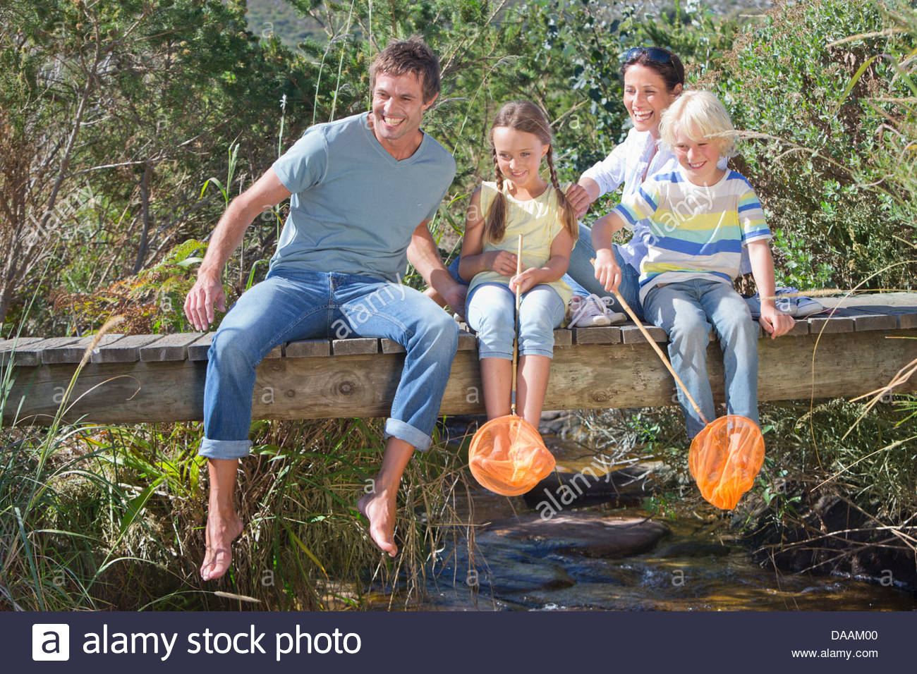 Happy family with fishing nets sitting on footbridge over stream - Stock Image