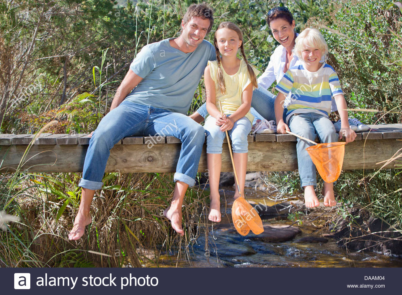 Portrait of smiling family with fishing nets sitting barefoot on footbridge over stream - Stock Image
