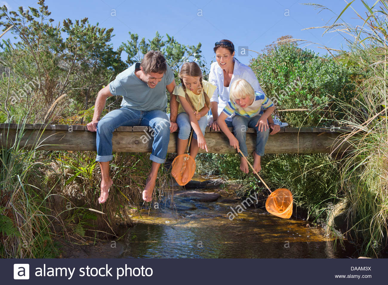 Family with fishing nets sitting barefoot on footbridge and looking down at stream - Stock Image
