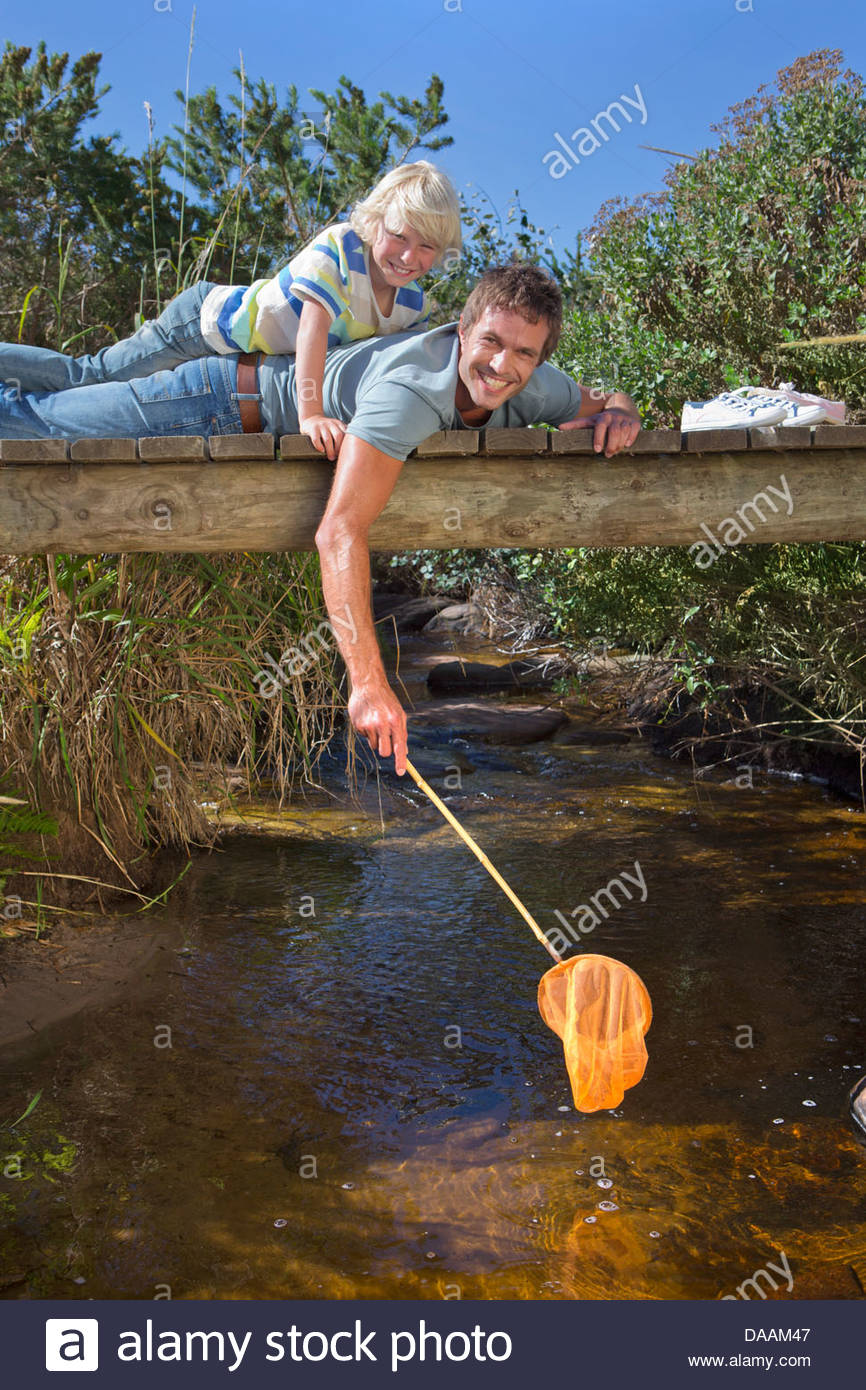 Portrait of smiling father and son laying on footbridge and dipping fishing net in stream - Stock Image
