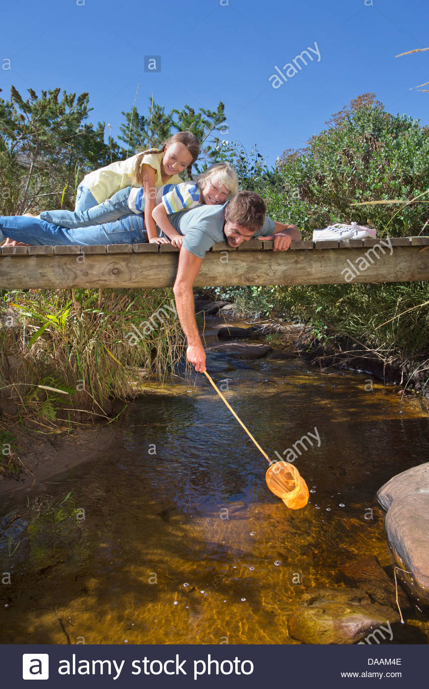 Father, daughter and son laying on footbridge and dipping fishing net in stream - Stock Image