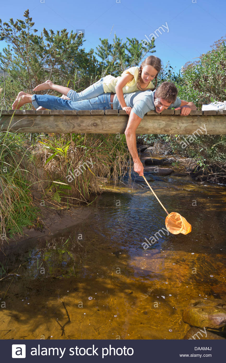 Father and daughter laying on footbridge and dipping fishing net in stream - Stock Image