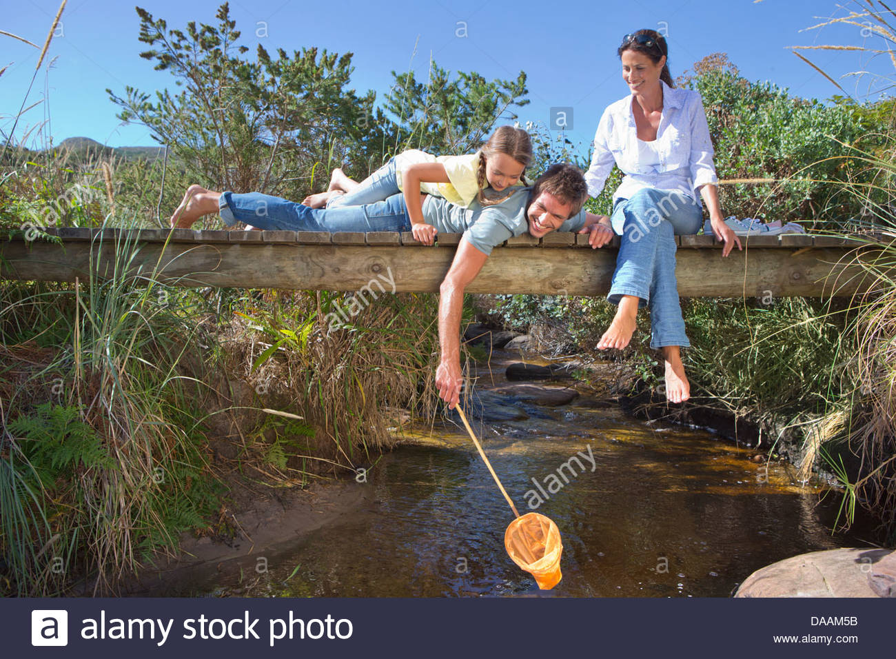 Family laying on footbridge and dipping fishing net in stream - Stock Image