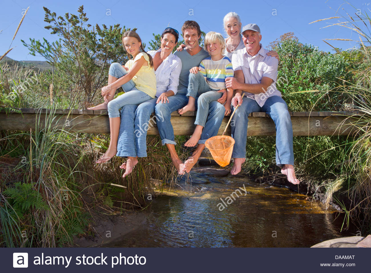 Portrait of smiling multi-generation family sitting barefoot on footbridge over stream - Stock Image