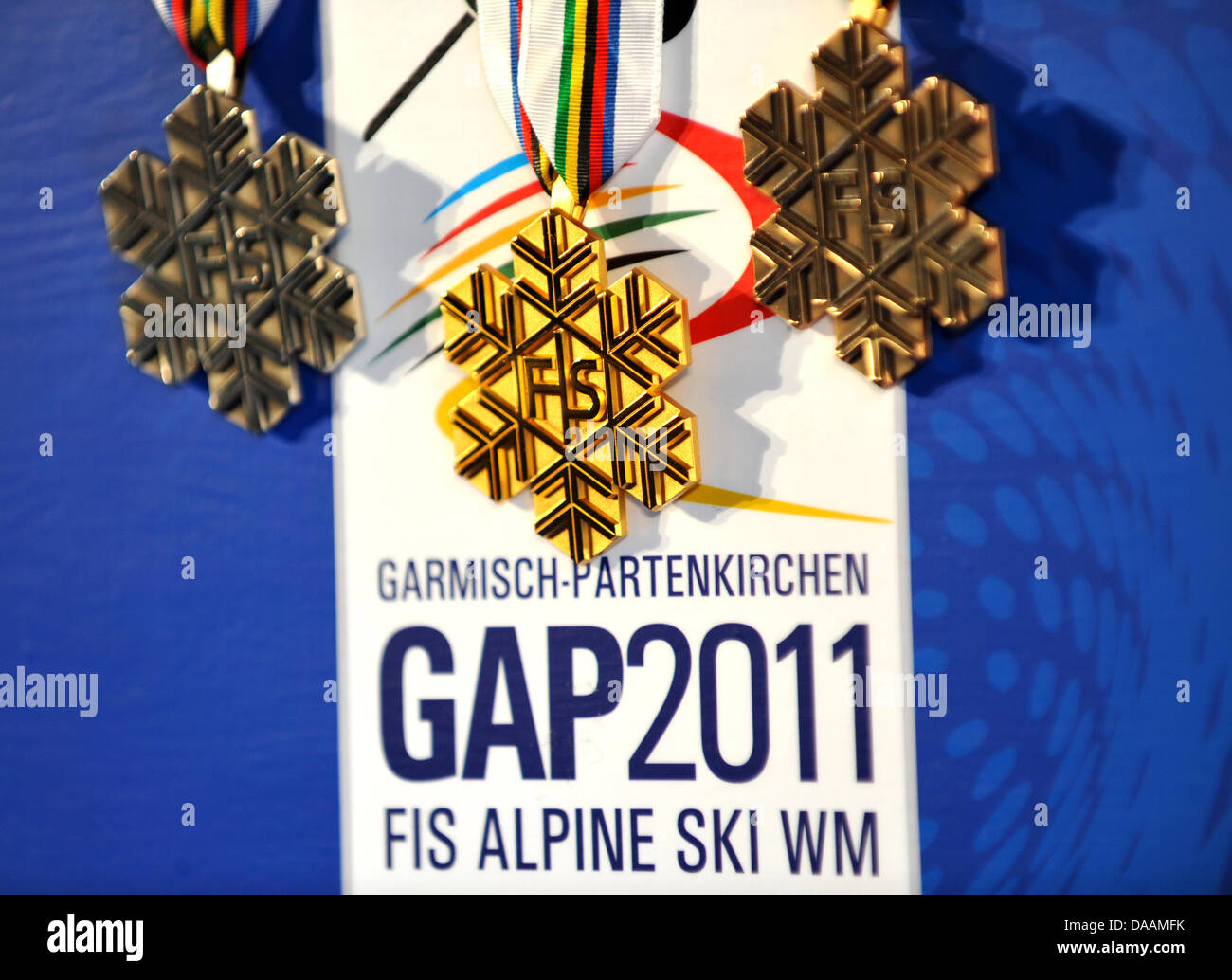 The medals of the International Ski Association FIS in silver (l-r), gold and bronze hang over the logo of the GAP - Stock Image