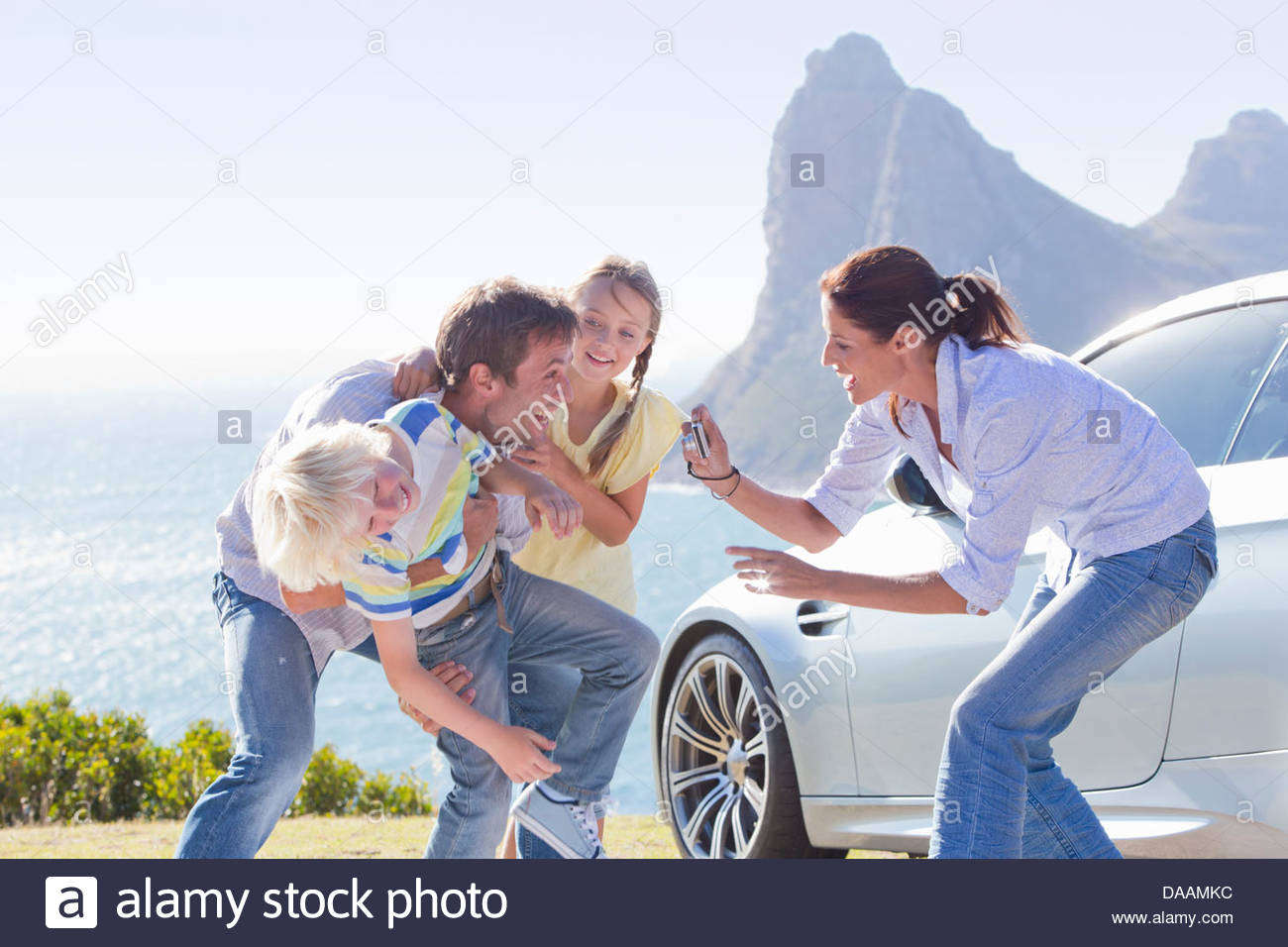 Mother photographing happy family playing outside car near ocean - Stock Image