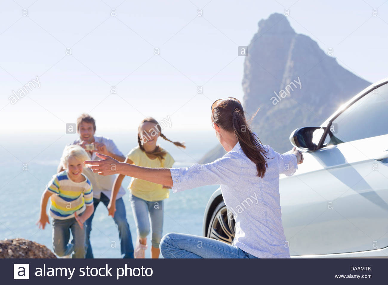 Family running toward woman with arms outstretched outside car near ocean - Stock Image